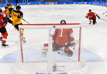 GANGNEUNG, SOUTH KOREA - FEBRUARY 20: Germany's Leonhard Pfoderl #83 gets the puck past Switzerland's Jonas Hiller #1 to score a first period goal with Philippe Furrer #54, Gaetan Haas #92 and Germany's Felix Schutz #55 looking on during qualification playoff round action at the PyeongChang 2018 Olympic Winter Games. (Photo by Matt Zambonin/HHOF-IIHF Images)